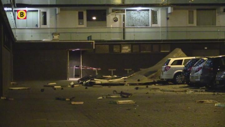 Dak waait van flat De Windvanger op geparkeerde auto's in Breda