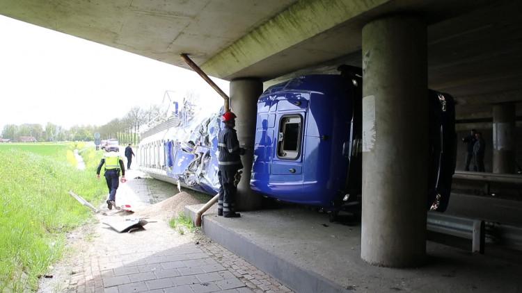 Vrachtwagen ramt viaduct in Hank en kantelt