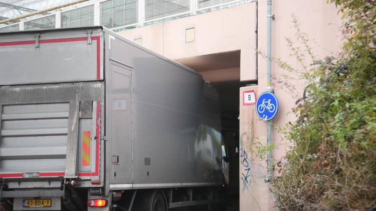Krakend komt de vrachtwagen onder de Boschdijktunnel vandaan