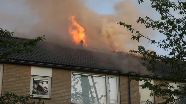 Vlammen slaan uit dak bij woningbrand in Oosterhout